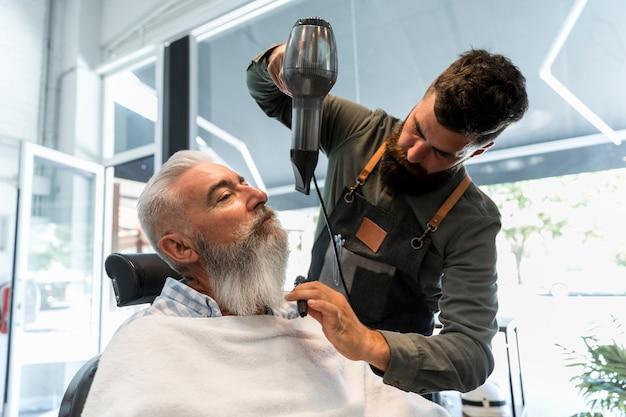 Männlicher friseur, der trockner für bart des älteren kunden verwendet