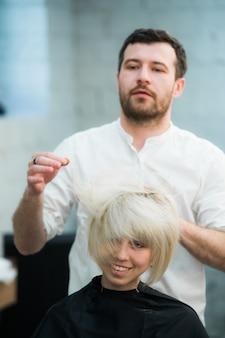 Männlicher friseur legt die haare der frau in einen friseursalon