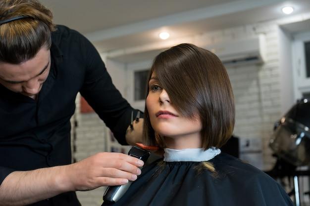 Männlicher friseur macht der hübschen frau im schönheitssalon einen haarschnitt.
