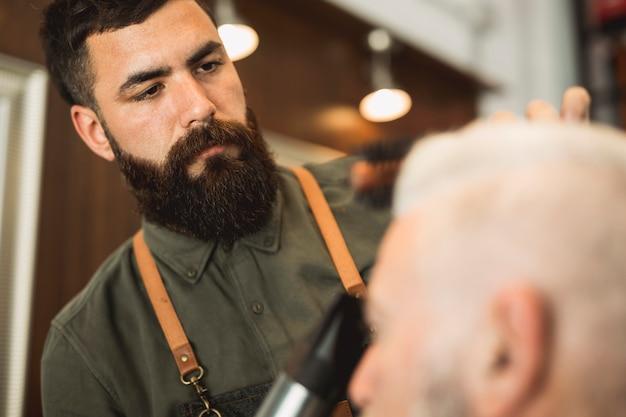 Männlicher friseur mit dem hairdryer, das mit älterem kunden arbeitet