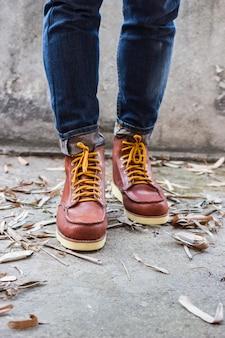 Männlicher fuß mit braunen lederschuhen und jeans