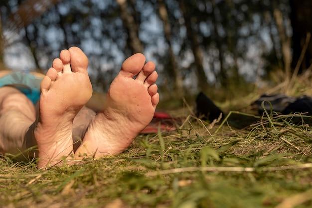 Männlicher fuß mit fersen auf gras im sonnigen sommer bei gutem wetter nahaufnahme kopienraum verfügbar