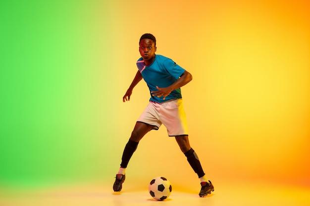 Männlicher fußball, fußballspielertraining in aktion lokalisiert auf gradientenstudio im neonlicht