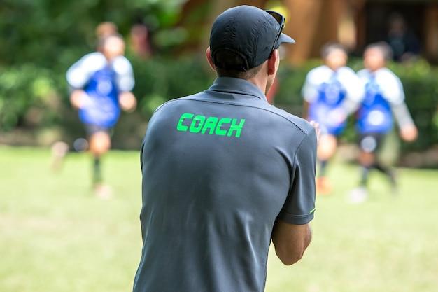 Männlicher fußball- oder fußballtrainer, der auf der seitenlinie aufpasst sein teamspiel steht