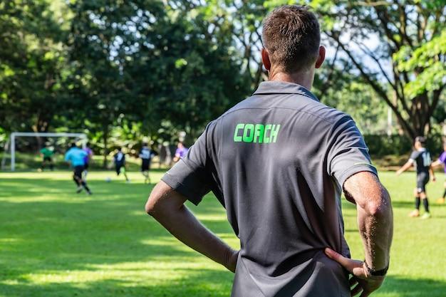 Männlicher fußball- oder fußballtrainer, der sein mannschaftsspiel an einem schönen fußballplatz aufpasst