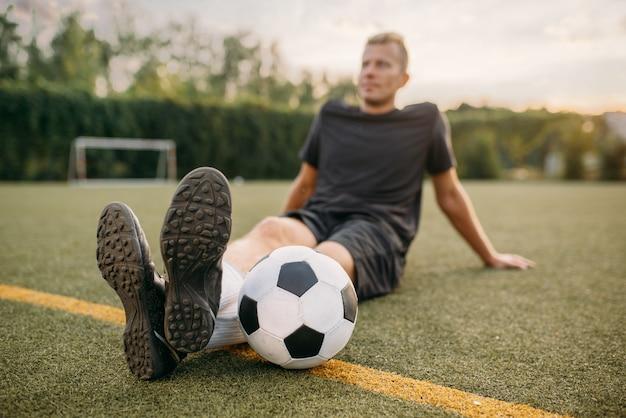 Männlicher fußballspieler mit ball, der auf dem gras auf dem feld sitzt. fußballer auf freiluftstadion, training vor dem spiel, fußballtraining