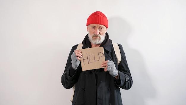 Männlicher gealterter landstreicher, obdachloser alter mann mit einem grauen bart in einem mantel und rotem hut mit einem zeichen für hilfe in seinen händen, isolierter weißer hintergrund