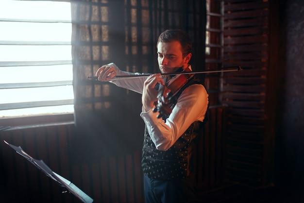 Männlicher geiger, der auf geige gegen das fenster spielt. geigermann mit musikinstrument
