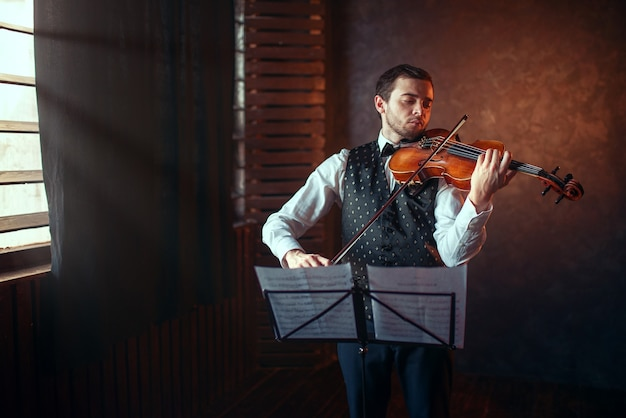 Männlicher geiger, der klassische musik auf geige spielt