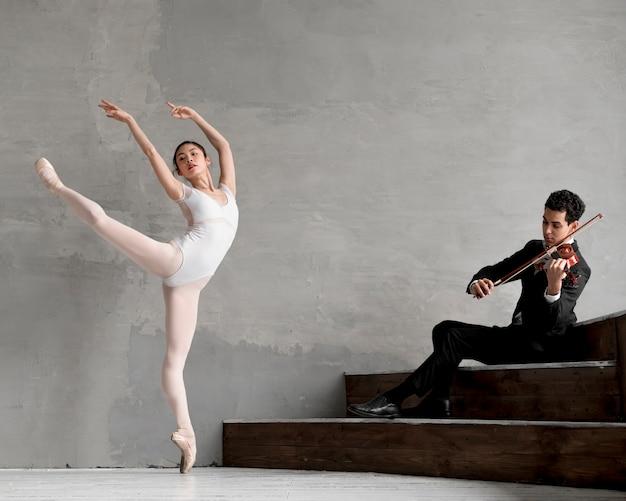 Männlicher geiger, der musik für ballerina spielt
