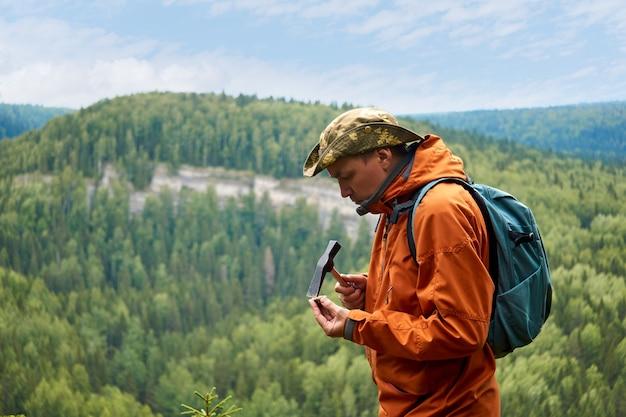 Männlicher geologe auf expedition untersucht einen stein mit einem hammer auf härte