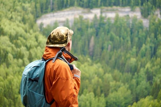 Männlicher geologe vor der kulisse einer bewaldeten berglandschaft