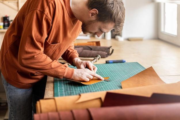 Männlicher gerber, der das schneideschema der tasche macht, die in der lederwerkstatt handgefertigt wird