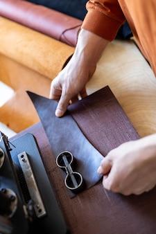 Männlicher gerber, der mit handpressgerät-maschinen-schnittmuster auf material-lederwerkstatt arbeitet
