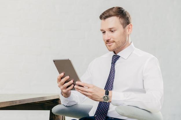 Männlicher geschäftsführer im weißen hemd und in der bindung, hält tablet-computer