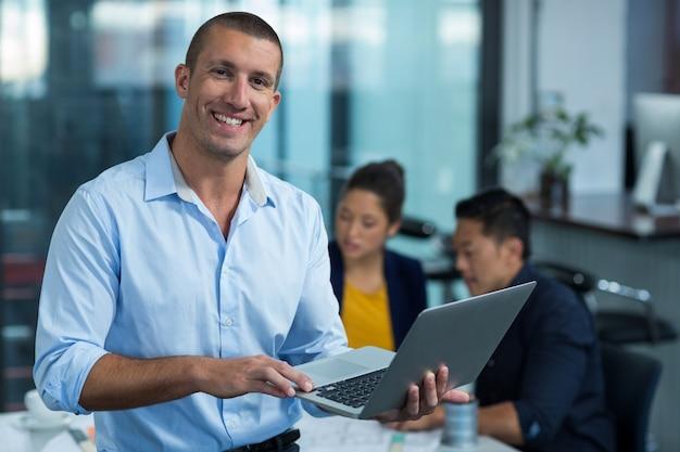 Männlicher geschäftsleiter, der laptop verwendet