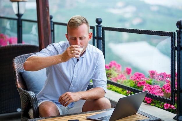 Männlicher geschäftsmann, der an laptop im café auf dem dach mit schönem panoramablick arbeitet. guy blogger trinkt kaffee und arbeitet auf reisen am computer
