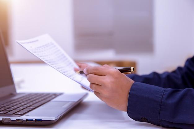 Männlicher geschäftsmann, der ein dokument liest, um eine bilanz mit der bank abzugeben.