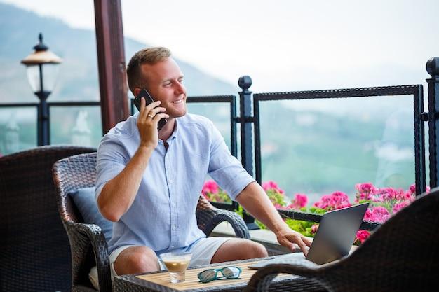 Männlicher geschäftsmann, der im urlaub an einem laptop mit schönem panoramablick arbeitet. erfolgreicher manager, der auf reisen kaffee trinkt und mit kaffee telefoniert