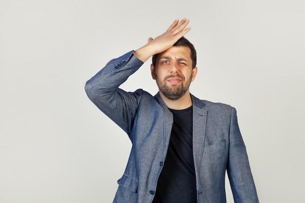 Männlicher geschäftsmann, der seine hand auf seine stirn legt und sich an etwas wichtiges erinnert