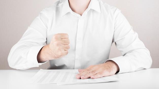 Männlicher geschäftsmann im zorn, in den fäusten, im finanzbericht