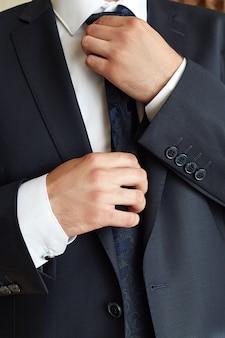 Männlicher geschäftsmann korrigiert eine gleichheit. manager trägt