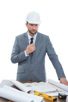 Männlicher geschäftsmanningenieur, der an einem denkenden schauen des gebäudeprojekts konzentriert arbeitet.