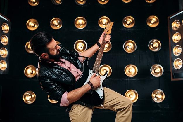 Männlicher gitarrist auf der bühne mit dekorationen der lichter