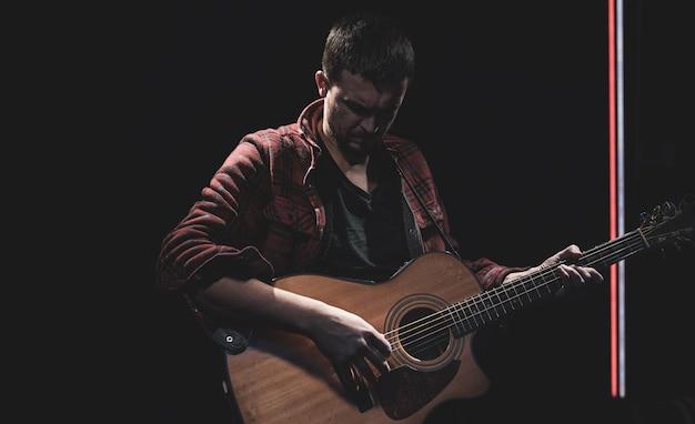 Männlicher gitarrist, der akustische gitarre im dunklen raum spielt.