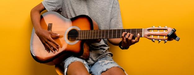 Männlicher gitarrist stimmt seine gitarre, bevor er jedes mal gitarre spielt. musikspielkonzept