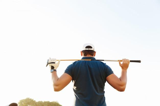 Männlicher golfer, der fahrer hält, während er auf grünem kurs steht