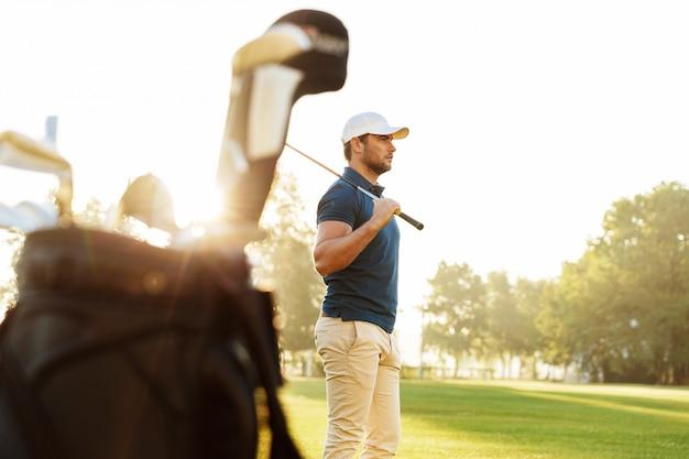 Männlicher golfer, der fahrer im stehen hält