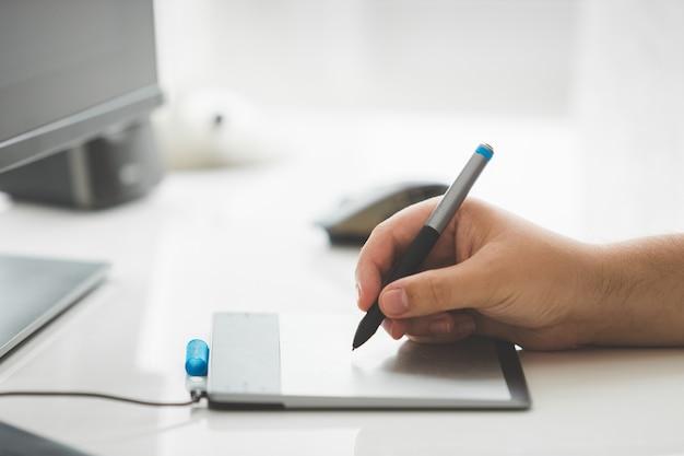 Männlicher grafikdesigner, der auf digitalem grafiktablett zeichnet
