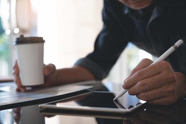 Männlicher grafikdesigner, der digitales tablett verwendet, das im büro arbeitet