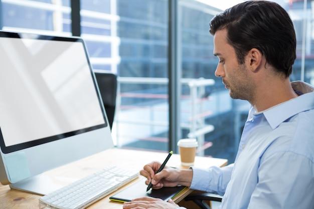Männlicher grafikdesigner, der grafiktablett am schreibtisch verwendet