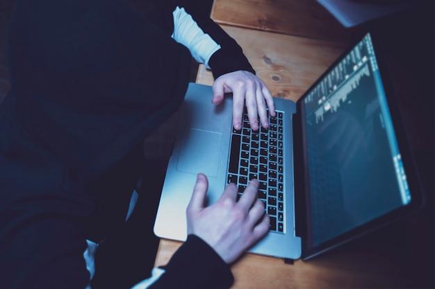 Männlicher hacker, der den laptop, die regierungsserver mit persönlichen daten brechend verwendet