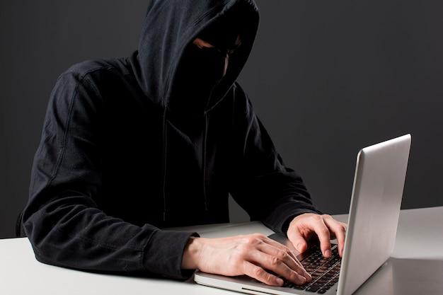 Männlicher hacker mit laptop
