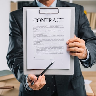 Männlicher handbehälter, der auf unterschriftenplatz auf einem vertragsdokument zeigt