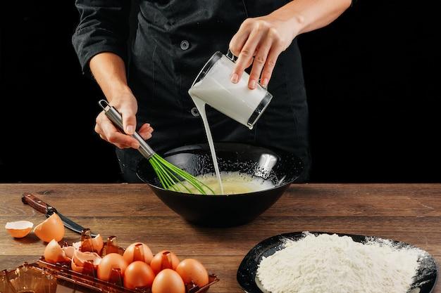 Männlicher handchef gießt die milch in eine platte auf einer hölzernen braunen tabelle in einer schwarzen schüssel.