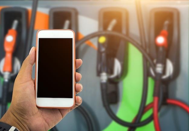 Männlicher handgriff weißer smartphone und kraftstoffpreis auf tankstellenhintergrund überprüfend