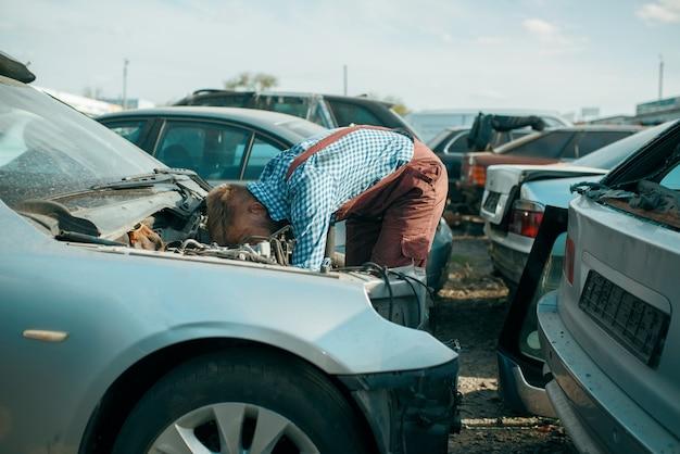 Männlicher handwerker arbeitet am autoschrottplatz. autoschrott, fahrzeugschrott, automüll, verlassener, beschädigter und zerquetschter transport