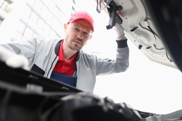 Männlicher handwerker, der unter motorhaube des autos schaut