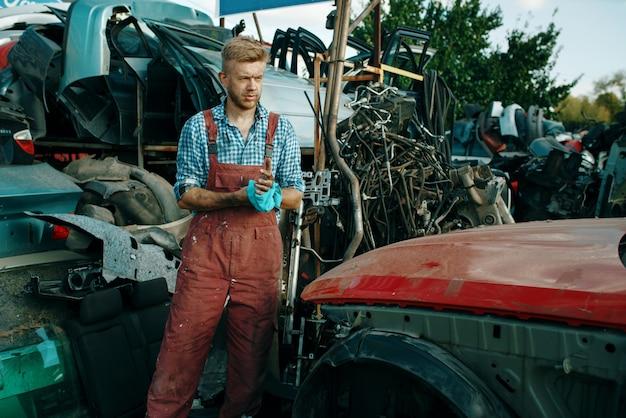 Männlicher handwerker mit handtuch auf autoschrottplatz. autoschrott, fahrzeugschrott, automüll. verlassener, beschädigter und zerquetschter transport, schrottplatz