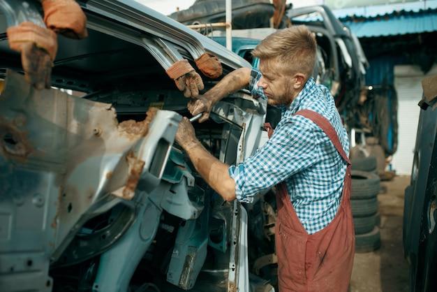 Männlicher handwerker wirft auf autoschrottplatz auf