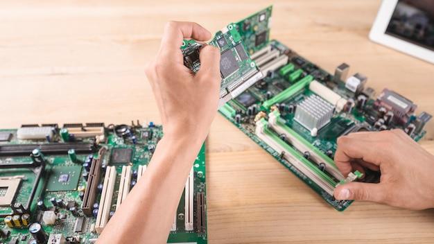 Männlicher hardware-ingenieur, der leiterplatte in gedächtnisschlitz einfügt