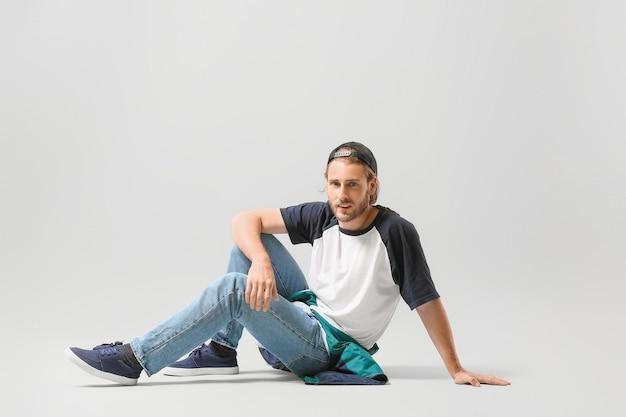 Männlicher hip-hop-tänzer auf heller oberfläche