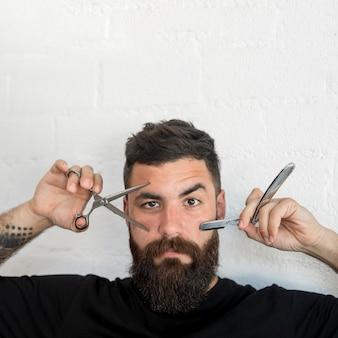 Männlicher hippie, der friseurwerkzeuge zeigt