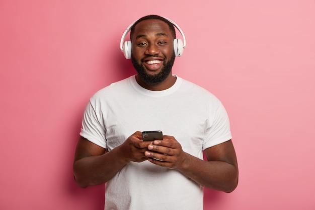 Männlicher hipster hört musik in drahtlosen kopfhörern isoliert