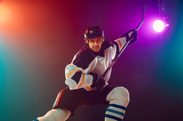 Männlicher hockeyspieler auf eisplatz und dunklem neonhintergrund, sport