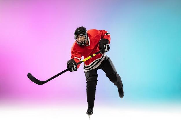 Männlicher hockeyspieler mit dem stock auf dem eisplatz und neonfarbenem hintergrund mit farbverlauf